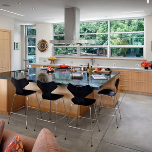 Contemporary kitchen inspiration - Example of a trendy u-shaped concrete floor and gray floor kitchen design in San Francisco with flat-panel cabinets, medium tone wood cabinets and an island