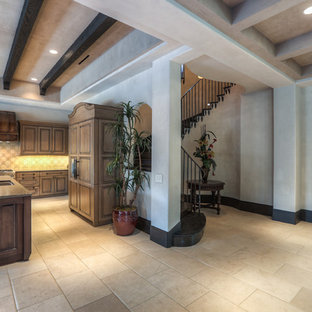Large tuscan l-shaped limestone floor and beige floor open concept kitchen photo in Houston with an undermount sink, raised-panel cabinets, medium tone wood cabinets, granite countertops, beige backsplash, mosaic tile backsplash, paneled appliances and an island