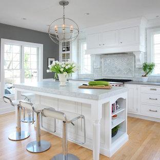Cette photo montre une grande cuisine parallèle chic avec un plan de travail en quartz modifié, des portes de placard blanches, une crédence grise, un placard avec porte à panneau encastré, un électroménager en acier inoxydable, un sol en bois clair, un îlot central et une crédence en marbre.