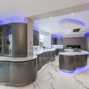 Aménagement d'une cuisine contemporaine avec un évier intégré, un placard à porte plane, des portes de placard grises, un plan de travail en surface solide, un électroménager en acier inoxydable, un sol en marbre et un îlot central.