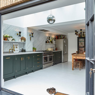Photo of a classic single-wall kitchen/diner in London with shaker cabinets, green cabinets, white splashback, stone slab splashback, stainless steel appliances, painted wood flooring, no island, white floors and white worktops.