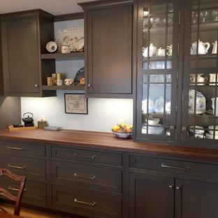ミルウォーキーの中サイズのエクレクティックスタイルのおしゃれなキッチン (アンダーカウンターシンク、シェーカースタイル扉のキャビネット、グレーのキャビネット、木材カウンター、白いキッチンパネル、セラミックタイルのキッチンパネル、シルバーの調理設備、無垢フローリング、アイランドなし、茶色い床) の写真