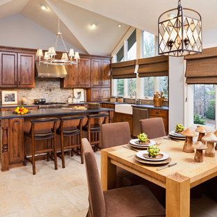 Photo of a large country u-shaped eat-in kitchen in New York with a farmhouse sink, raised-panel cabinets, dark wood cabinets, granite benchtops, multi-coloured splashback, slate splashback, stainless steel appliances, travertine floors, with island, beige floor and black benchtop.