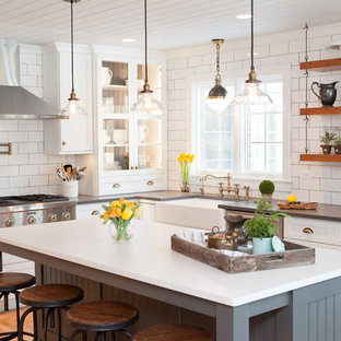 Mid-sized country u-shaped kitchen in Chicago with a farmhouse sink, recessed-panel cabinets, white cabinets, quartz benchtops, multi-coloured splashback, subway tile splashback, stainless steel appliances, an island and medium hardwood floors.