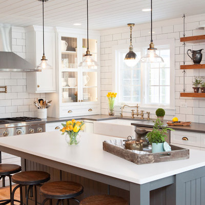Example of a mid-sized country u-shaped medium tone wood floor kitchen design in Chicago with a farmhouse sink, recessed-panel cabinets, white cabinets, quartz countertops, multicolored backsplash, subway tile backsplash, stainless steel appliances and an island