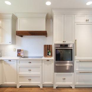 バンクーバーの中サイズのシャビーシック調のおしゃれなキッチン (アンダーカウンターシンク、シェーカースタイル扉のキャビネット、白いキャビネット、クオーツストーンカウンター、白いキッチンパネル、モザイクタイルのキッチンパネル、パネルと同色の調理設備、無垢フローリング、アイランドなし) の写真