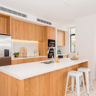 Inspiration for a mid-sized contemporary galley kitchen in Christchurch with an undermount sink, flat-panel cabinets, light wood cabinets, quartz benchtops, white splashback, glass sheet splashback, stainless steel appliances, porcelain floors, with island, beige floor and white benchtop.