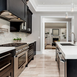 Photo of a transitional l-shaped kitchen in Toronto with an undermount sink, shaker cabinets, dark wood cabinets, solid surface benchtops, white splashback, glass tile splashback, stainless steel appliances and marble floors.