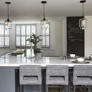 Design ideas for a large contemporary galley open plan kitchen in London with an integrated sink, recessed-panel cabinets, grey cabinets, marble benchtops, metallic splashback, mirror splashback, stainless steel appliances, dark hardwood floors, a peninsula, brown floor and white benchtop.