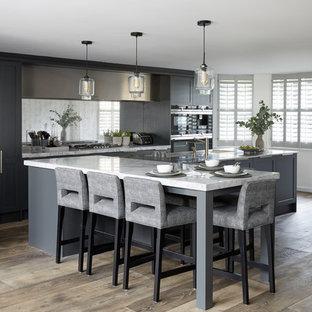 Idéer för stora funkis vitt kök, med en integrerad diskho, luckor med infälld panel, grå skåp, marmorbänkskiva, stänkskydd med metallisk yta, spegel som stänkskydd, rostfria vitvaror, mörkt trägolv, en halv köksö och brunt golv