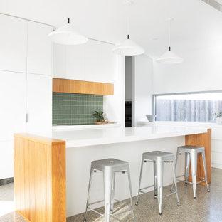 Design ideas for a mid-sized modern l-shaped open plan kitchen in Melbourne with flat-panel cabinets, white cabinets, green splashback, with island, grey floor, white benchtop, an undermount sink, quartz benchtops, ceramic splashback, panelled appliances and concrete floors.