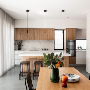 This is an example of a mid-sized contemporary galley open plan kitchen in Perth with flat-panel cabinets, medium wood cabinets, quartz benchtops, marble splashback, concrete floors and with island.