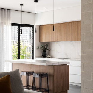 Inspiration for a mid-sized midcentury galley open plan kitchen in Perth with flat-panel cabinets, medium wood cabinets, quartz benchtops, marble splashback, concrete floors and with island.