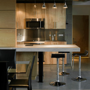 Mid-sized minimalist galley concrete floor eat-in kitchen photo in Phoenix with an undermount sink, flat-panel cabinets, light wood cabinets, concrete countertops, metallic backsplash, metal backsplash, stainless steel appliances and an island