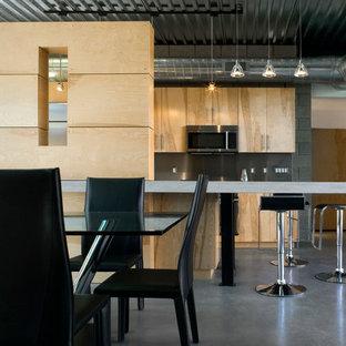 Inredning av ett modernt mellanstort kök, med en undermonterad diskho, släta luckor, skåp i ljust trä, bänkskiva i betong, stänkskydd med metallisk yta, stänkskydd i metallkakel, rostfria vitvaror, betonggolv och en köksö