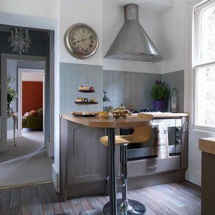 Photo of a small traditional kitchen in Other with grey cabinets, wood worktops, grey splashback, stainless steel appliances, a breakfast bar and multi-coloured floors.