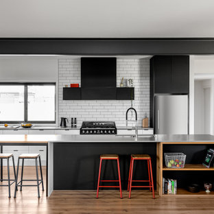 This is an example of a contemporary kitchen in Other with an undermount sink, flat-panel cabinets, white cabinets, white splashback, subway tile splashback, stainless steel appliances, medium hardwood floors, with island and grey benchtop.