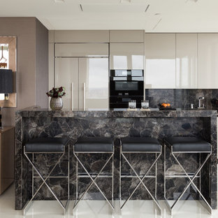 Photo of a small contemporary galley open plan kitchen in London with flat-panel cabinets, black splashback, stone slab splashback, an island, white floors, black worktops, an integrated sink, grey cabinets, black appliances and porcelain flooring.