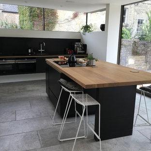 他の地域の大きいモダンスタイルのおしゃれなキッチン (フラットパネル扉のキャビネット、濃色木目調キャビネット、木材カウンター、黒いキッチンパネル、石タイルのキッチンパネル、緑のキッチンカウンター) の写真