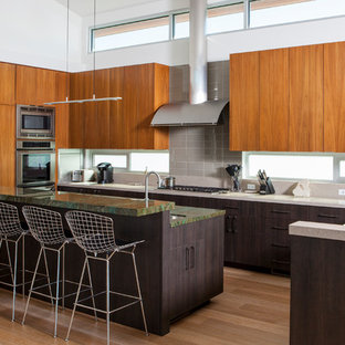 Design ideas for a contemporary u-shaped kitchen in Los Angeles with an undermount sink, flat-panel cabinets, medium wood cabinets, window splashback, stainless steel appliances, medium hardwood floors, with island, brown floor and green benchtop.