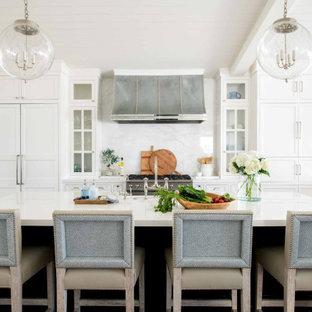 Пример оригинального дизайна: большая угловая кухня в морском стиле с фасадами с утопленной филенкой, белыми фасадами, белым фартуком, фартуком из каменной плиты, техникой под мебельный фасад, паркетным полом среднего тона, островом, коричневым полом, белой столешницей и потолком из вагонки
