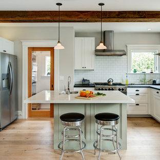 サンフランシスコの中サイズのエクレクティックスタイルのおしゃれなキッチン (エプロンフロントシンク、シェーカースタイル扉のキャビネット、白いキャビネット、ソープストーンカウンター、白いキッチンパネル、サブウェイタイルのキッチンパネル、シルバーの調理設備の、淡色無垢フローリング、茶色い床) の写真