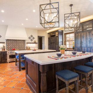 デンバーの広いサンタフェスタイルのおしゃれなキッチン (エプロンフロントシンク、シェーカースタイル扉のキャビネット、濃色木目調キャビネット、白いキッチンパネル、シルバーの調理設備、テラコッタタイルの床、赤い床、白いキッチンカウンター) の写真