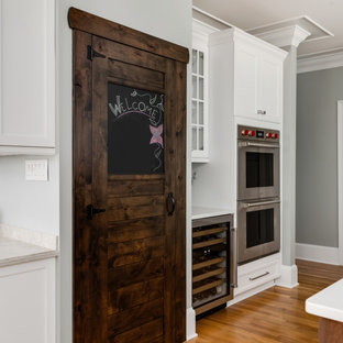 Inspiration for a medium sized classic l-shaped kitchen pantry in Charlotte with a belfast sink, shaker cabinets, white cabinets, engineered stone countertops, brown splashback, porcelain splashback, stainless steel appliances, light hardwood flooring, an island, brown floors and yellow worktops.