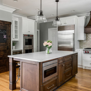 Photo of a medium sized traditional l-shaped kitchen/diner in Charlotte with a belfast sink, shaker cabinets, white cabinets, engineered stone countertops, brown splashback, porcelain splashback, stainless steel appliances, light hardwood flooring, an island, brown floors and yellow worktops.