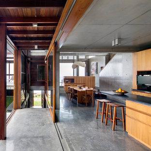 Свежая идея для дизайна: кухня-гостиная в современном стиле с светлыми деревянными фасадами, бетонным полом, врезной раковиной, плоскими фасадами, черным фартуком и островом - отличное фото интерьера