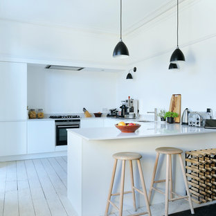 Cette photo montre une cuisine scandinave en U avec un placard à porte plane, des portes de placard blanches, un électroménager en acier inoxydable, un sol en bois clair et une péninsule.