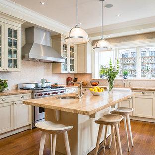 トロントのトランジショナルスタイルのおしゃれなキッチン (エプロンフロントシンク、シェーカースタイル扉のキャビネット、ベージュのキャビネット、タイルカウンター、ベージュキッチンパネル、シルバーの調理設備の、無垢フローリング、茶色い床、茶色いキッチンカウンター) の写真