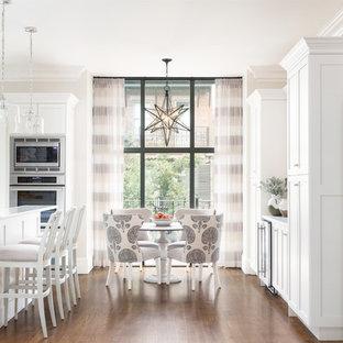 Idee per una cucina abitabile tradizionale con ante in stile shaker, ante bianche, elettrodomestici in acciaio inossidabile, parquet scuro e pavimento marrone