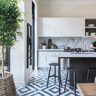 Foto di una cucina minimalista con lavello sottopiano, paraspruzzi in lastra di pietra, elettrodomestici in acciaio inossidabile e pavimento in cementine
