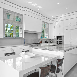Large contemporary kitchen ideas - Inspiration for a large contemporary l-shaped gray floor kitchen remodel in Miami with flat-panel cabinets, white cabinets, an undermount sink, gray backsplash, glass sheet backsplash, stainless steel appliances, two islands and white countertops