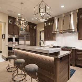 Design ideas for a large modern u-shaped open plan kitchen in Salt Lake City with a submerged sink, recessed-panel cabinets, dark wood cabinets, granite worktops, white splashback, glass tiled splashback, stainless steel appliances, light hardwood flooring and an island.