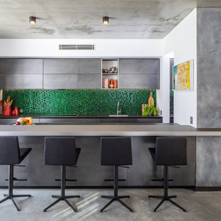 This is an example of a large contemporary open plan kitchen in Perth with an undermount sink, green splashback, glass tile splashback, panelled appliances, concrete floors, with island and grey benchtop.