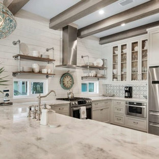 Mid-sized coastal enclosed kitchen designs - Mid-sized beach style u-shaped light wood floor and brown floor enclosed kitchen photo in Miami with a farmhouse sink, shaker cabinets, white cabinets, quartzite countertops, white backsplash, wood backsplash, stainless steel appliances, a peninsula and white countertops