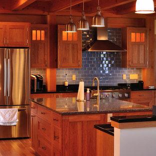 Cette image montre une très grand cuisine traditionnelle en L avec un évier encastré, un placard à porte affleurante, des portes de placard en bois brun, un plan de travail en granite, une crédence noire, un électroménager en acier inoxydable, un sol en bois clair et 2 îlots.