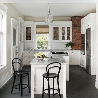 Inredning av ett amerikanskt grå grått kök, med luckor med glaspanel, vita skåp, marmorbänkskiva, vitt stänkskydd, rostfria vitvaror, en köksö, grått golv, en undermonterad diskho, stänkskydd i tunnelbanekakel och skiffergolv