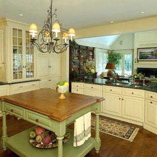フィラデルフィアの大きいトラディショナルスタイルのおしゃれなキッチン (ダブルシンク、レイズドパネル扉のキャビネット、ベージュのキャビネット、御影石カウンター、ベージュキッチンパネル、セラミックタイルのキッチンパネル、パネルと同色の調理設備、濃色無垢フローリング) の写真