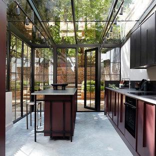Cette photo montre une cuisine chic avec un évier 1 bac, des portes de placard noires, un électroménager noir, béton au sol, un îlot central, un sol gris et un plan de travail gris.