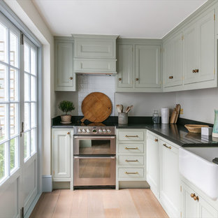 Design ideas for a small traditional l-shaped separate kitchen in London with a farmhouse sink, recessed-panel cabinets, green cabinets, granite benchtops, white splashback, ceramic splashback, no island, beige floor, stainless steel appliances and light hardwood floors.