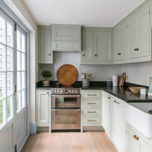 ロンドンの小さいトラディショナルスタイルのおしゃれなキッチン (エプロンフロントシンク、落し込みパネル扉のキャビネット、緑のキャビネット、御影石カウンター、白いキッチンパネル、セラミックタイルのキッチンパネル、アイランドなし、ベージュの床、シルバーの調理設備、淡色無垢フローリング) の写真