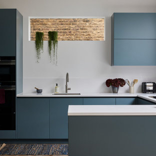 This is an example of a contemporary u-shaped open plan kitchen in London with flat-panel cabinets, blue cabinets, composite countertops, white splashback, engineered quartz splashback, medium hardwood flooring, white worktops, a submerged sink, black appliances, a breakfast bar and brown floors.
