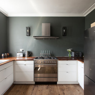 This is an example of a contemporary u-shaped kitchen in London with a double-bowl sink, flat-panel cabinets, white cabinets, wood worktops, stainless steel appliances, medium hardwood flooring, brown floors and brown worktops.