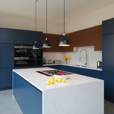 Large trendy l-shaped concrete floor and gray floor open concept kitchen photo in London with flat-panel cabinets, blue cabinets, white backsplash, an island, white countertops, an integrated sink, quartzite countertops, stone slab backsplash and paneled appliances