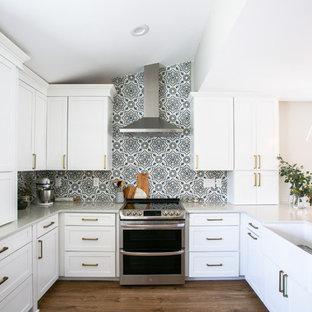 Idéer för att renovera ett mellanstort vintage grå grått kök, med en rustik diskho, skåp i shakerstil, vita skåp, bänkskiva i kvarts, flerfärgad stänkskydd, stänkskydd i cementkakel, rostfria vitvaror, vinylgolv, en halv köksö och brunt golv