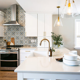 Inspiration for a mid-sized transitional u-shaped eat-in kitchen in Denver with a farmhouse sink, shaker cabinets, white cabinets, quartz benchtops, multi-coloured splashback, cement tile splashback, stainless steel appliances, vinyl floors, a peninsula, brown floor and grey benchtop.