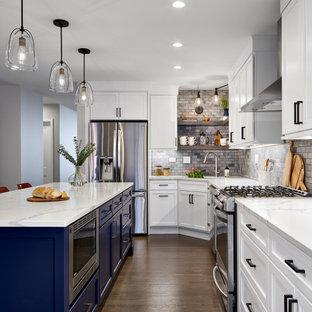 シカゴのトランジショナルスタイルのおしゃれなキッチン (白いキャビネット、大理石カウンター、グレーのキッチンパネル、大理石のキッチンパネル、シルバーの調理設備、無垢フローリング、茶色い床、白いキッチンカウンター) の写真